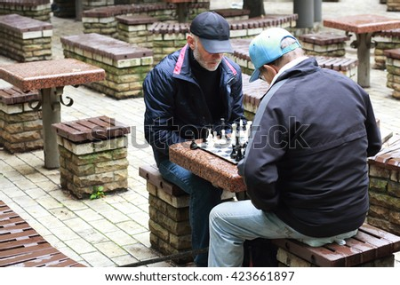 two elderly male retirees playing chess in the park. Active retired people, Recreation, outdoor