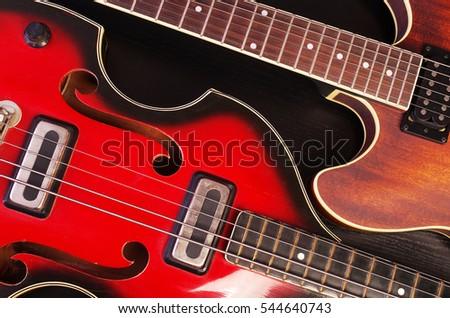 Two electric guitars on black.