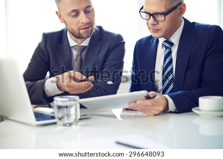 Two elegant men using digital tablet at meeting