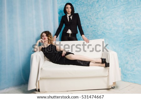 Two fashionable young girls sitting on the armchair