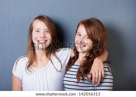 Two female best friends posing over the grey background