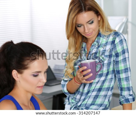 Two female designers in office looking at laptop computer display smiling. Young colleague at workplace showing her creative work for appreciation. Creative people or advertising business concept