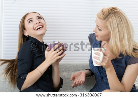 Two female friends talking and laughing together sitting on sofa during coffee break.