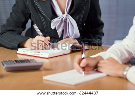 two female hands that taking notes at the meeting