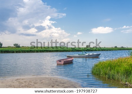 Two fishing boats on a river in sunny summer day on the background of blue sky with clouds