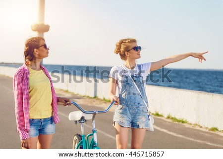 Two friends out for a bike ride at the seaside. Stylish casual outfit. Evening sunset, students, happy time, toned colors.