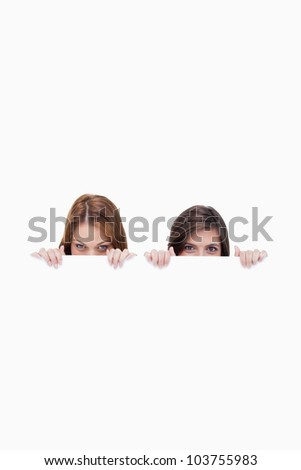 Two friends secretly hiding behind a blank poster against a white background