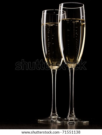 Two full glasses of champagne over dark background
