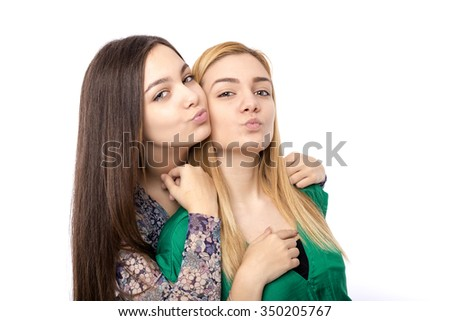 Two funny affectionate teenage friends -blonde and brunette- sending kisses over white background