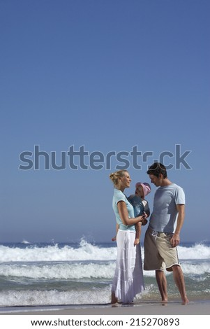 Two generation family standing on beach at water's edge, mother holding daughter (2-4)