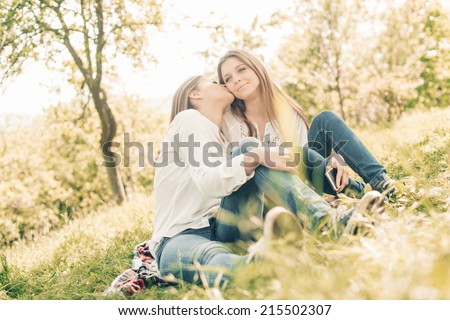 two girlfriends lying down on grass laughing having good time