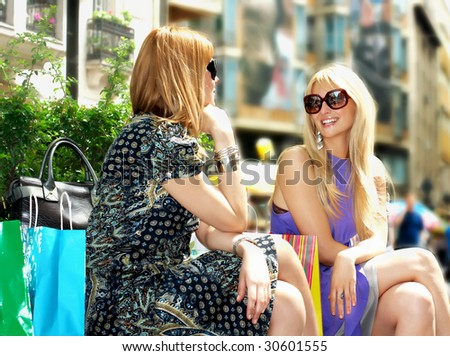 Two girlfriends relax after shopping in city.