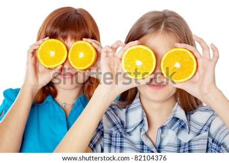 Two girls are looking through oranges. Isolated on white background