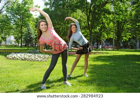 Two girls doing an exercise tilts aside outdoors in the park against the backdrop of greenery