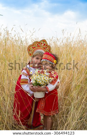 Two girls in the Russian national sundresses and kokoshniks about wheat field with a bouquet of camomiles