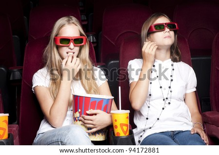 two girls look three-dimensional cinema, sitting in the glasses, eat popcorn, drink drink