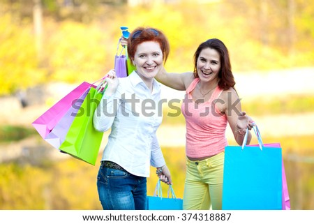 Two girls with bags after shopping in the park