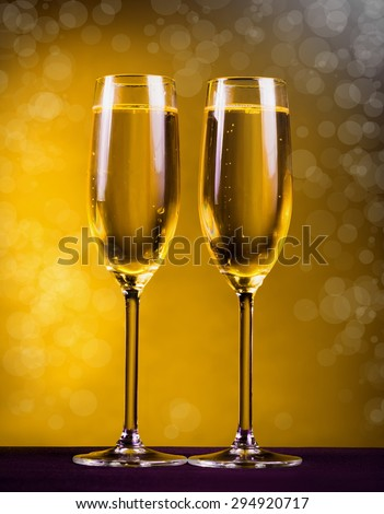 two glasses flutes golden champagne yellow background holiday Christmas new Year Valentine Day event luxury life drink night