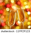 Two glasses of champagne with lights in the background. very shallow depth of field. - stock photo