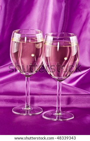 Two glasses of white wine on a lilac background