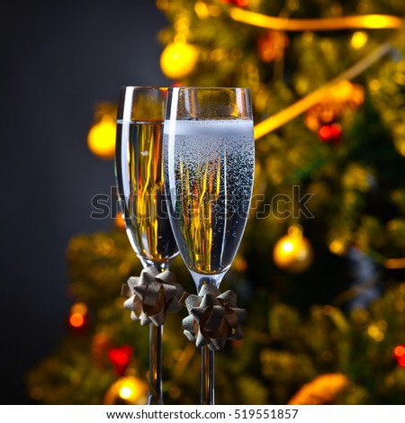 Two glasses with champagne and Christmas ornaments , focus on foreground