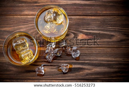 Two glasses with ice and whiskey on wooden background