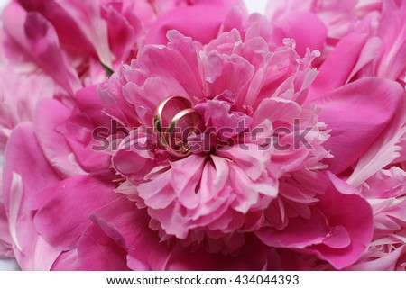 two gold wedding rings and pink peonies