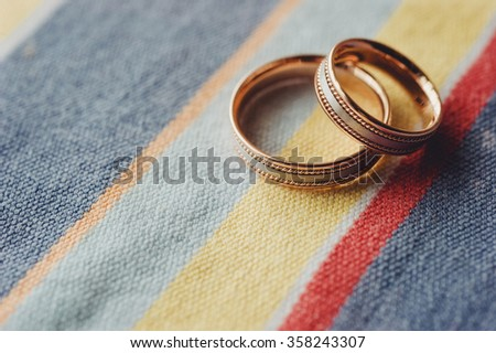 Two gold wedding rings lying on colored cloth