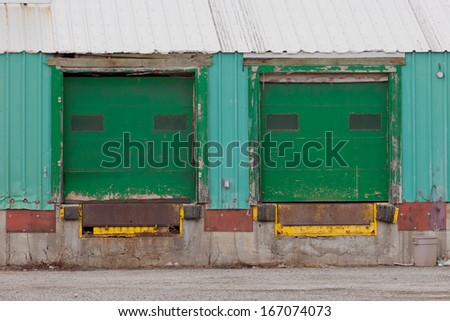 Two green painted shuttered doors for loading in a prefabricated metal clad warehouse building
