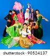 Two guys and seven girls dressed in costumes of different nations of the world on blue background - stock photo
