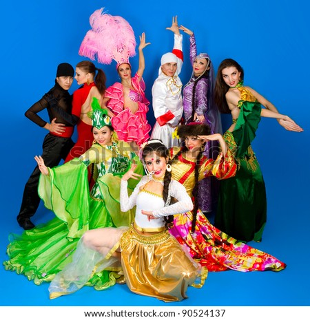 Two guys and seven girls dressed in costumes of different nations of the world on blue background