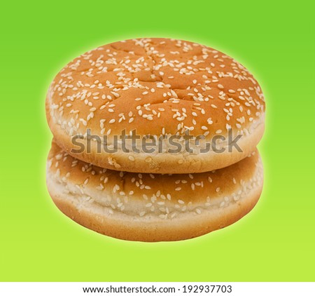 Two hamburger bun with sesame seeds on green background.