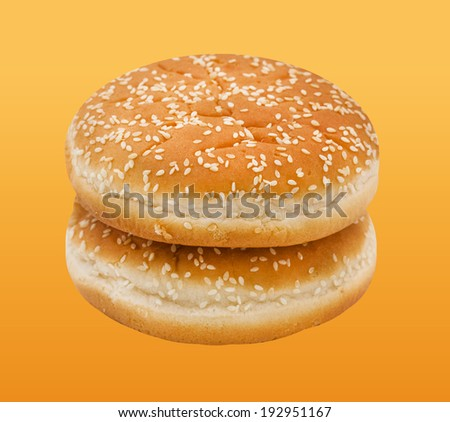 Two hamburger bun with sesame seeds on orange  background.