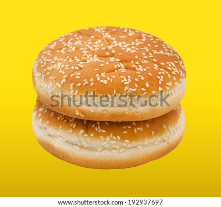 Two hamburger bun with sesame seeds on yellow background.