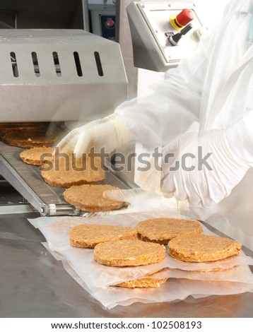 two hands at a hamburger machine in a meat factory