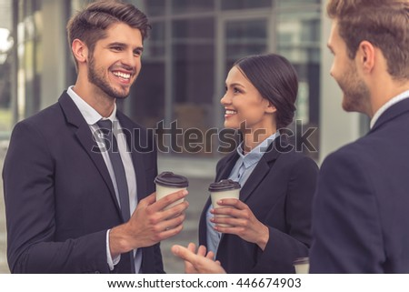 Two handsome young businessmen and lady in classic suits are holding cups of coffee, talking and smiling, standing outside the office building