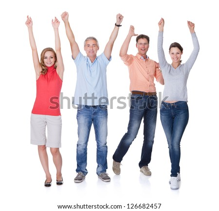 Two happy attractive couples in casual clothes and jeans celebrating raising their arms in the air and shouting on white