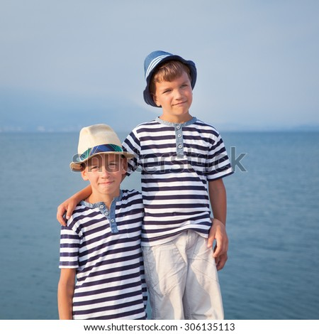 Two happy brothers hug and look at ships, yacht at sea
