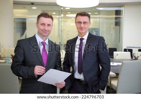 Two happy businessmen standing with a blank sheet of paper in conference hall