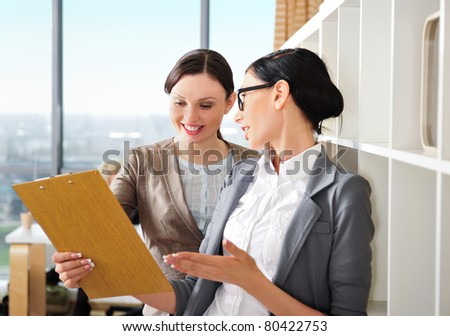 Two happy caucasian business women reading documents at their office against window