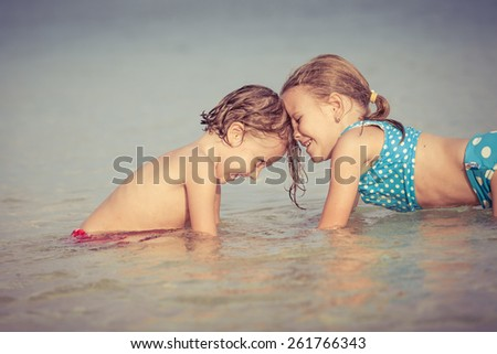 Two happy children  playing on the beach at the day time