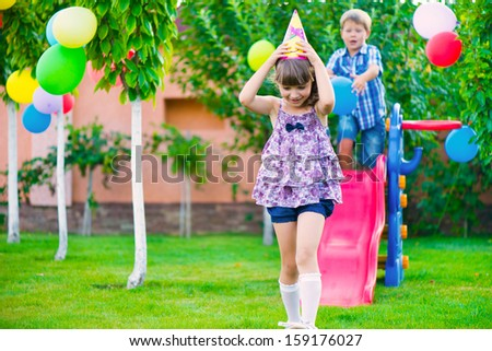 Two happy children sliding at playground during birthday party