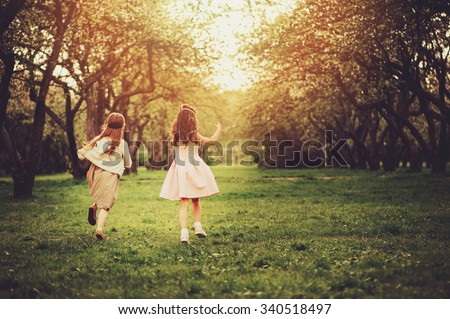 two happy dressy girls running on spring walk, back view, friendship concept, soft focus