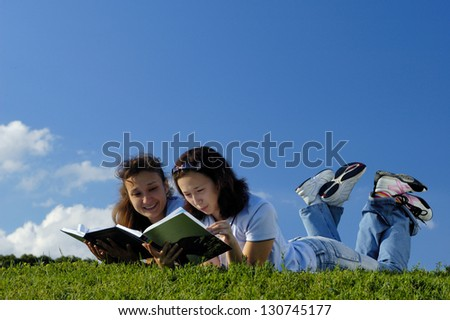 Two happy girls reading books in the nature studying outside in a park lying on green grass