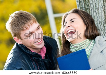 Two Happy laughing young students in autumn outdoors