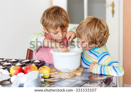 Two happy little blond kid boys, friends baking apple cake in domestic kitchen. Children having fun with working with mixer, eggs and fruits. Tasting dough