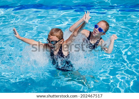 two happy little girls playing  in the swimming pool at the day time
