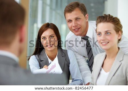 Two happy managers looking at business partner at meeting