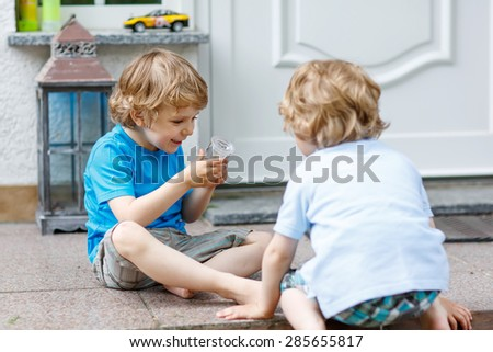 Two happy sibling boys having fun and playing together in summer garden, outdoors. On warm sunny day. Selective focus on one child.