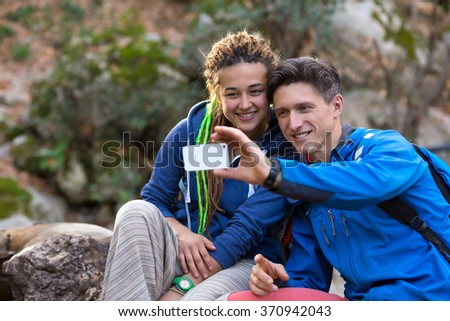 Two Hikers Handsome Man and Cute Girl with Dreadlocks Hair Style smiling taking self Portrait Photo with Camera of smart phone on Hike in Spring Time Forest